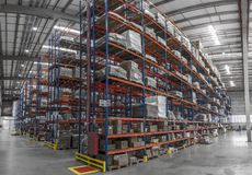 Logistic shed and distribution boxes workers and forklift in operation. Rack stock photography