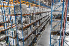 Logistic shed and distribution boxes workers and forklift in operation. Rack royalty free stock photography