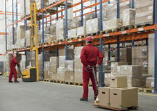 Logistic - workers in storehouse. Two workers in uniforms and safety helmets working in storehouse Royalty Free Stock Images
