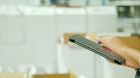 Logistica e contabilità di magazzino Donna che lavora con una compressa sui precedenti di una pila di scatole bianche video d archivio