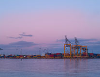 Logistics. Cranes and freight containers at the docks at sunset Stock Image