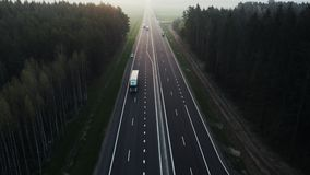 Logistics company delivers the goods. Postage delivery. Road through the green spruce forest, aerial view. Clean road with new road markings. Forest landscape