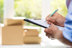 Logistics - delivery service man writing documents. On clipboard Royalty Free Stock Images