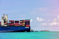 Cargo containers ship. Logistics import export background of container Cargo ship in seaport  by tugboat navigation assistant on blue sky, fright Transportation Royalty Free Stock Image