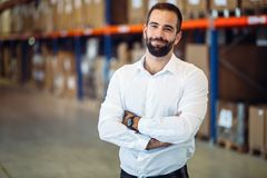 Logistics manager posing in warehouse. Smart and handsome logistics manager warehouse portrait Stock Image