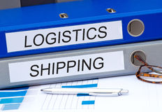Logistics and shipping. Two white labels 'logistics' and 'shipping' written in black uppercase letters attached to blue and silver binders placed on a desk with Royalty Free Stock Photography