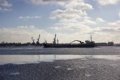 Logistics and transportation  Cargo ship with ports crane bridge coming in port Stock Photos