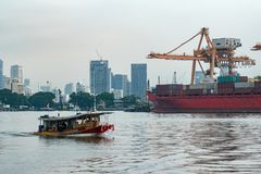 Logistics and transportation of Container Cargo ship and Crane Bridge with building cityscape background. Import and Export royalty free stock photography