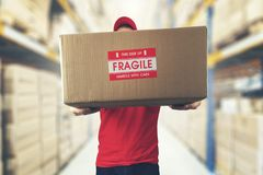 Logistics warehouse worker holding package with fragile items stock photos