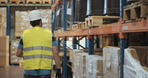 Logistics worker inspecting items in a large warehouse stock video footage