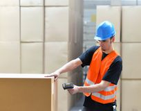 Logistics worker - man scans parcels of goods and prepares the d. Ispatch in a company`s department store royalty free stock photography