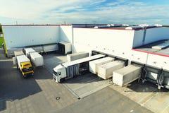Logistiek en goederenopslag - lading en het leegmaken van goederen voor vervoer per vrachtwagen royalty-vrije stock foto's