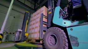 Logistiek en verschepende faciliteit De dozen en de goederen van de vorkheftruckbeweging in pakhuis 4K stock footage