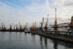 Logistik och trans. av behållarelastfartyg- och lastnivån med den arbetande kranbron i skeppsvarv på skymning royaltyfri fotografi