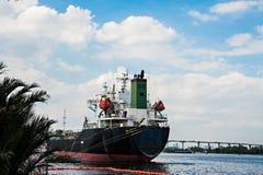 Logistycznie pojęcie, czarny statek parkujący w rzece Obraz Stock