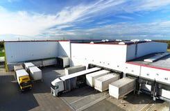 Logistyki i towarowy magazyn - ładujący i rozładowywający towary dla zdjęcia stock