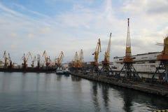 Logistyki i transport zbiornika ładunku statek i ładunku samolot z pracującym żurawia mostem w stoczni przy zmierzchem fotografia royalty free