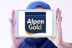 Alpen gold brand logo. Logo of alpen gold on samsung tablet holded by arab muslim woman royalty free stock image