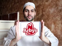 Arbys fast food logo. Logo of arbys fast food restaurants on samsung tablet holded by arab muslim man Royalty Free Stock Photo