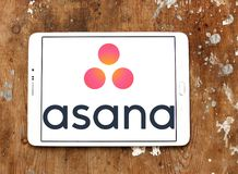 Asana software logo. Logo of Asana software on samsung tablet on wooden background. Asana is a web and mobile application designed to help teams track their work Royalty Free Stock Images