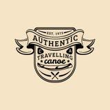 Logo autentico del campo di vettore Segno turistico con la canoa e le pagaie disegnate a mano Retro distintivo dei pantaloni a vi Fotografia Stock