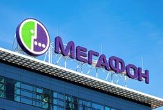 Logo av MegaFon mot blå himmel Royaltyfri Foto