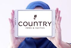 Country Inns and Suites logo. Logo of Country Inns and Suites on samsung tablet holded by arab muslim woman. Country Inns and Suites by Radisson is an American royalty free stock photography
