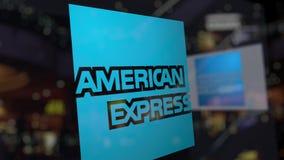 Logo d'American Express sur le verre contre le centre brouillé d'affaires Rendu 3D éditorial Photographie stock libre de droits