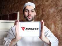 Dainese brand logo. Logo of Dainese company on samsung tablet holded by arab muslim man. Dainese is an Italian manufacturer of protective gear and clothing for stock images