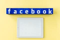 Logo de Facebook fait à partir des cubes bleus avec le comprimé numérique et l'écran vide Photos libres de droits