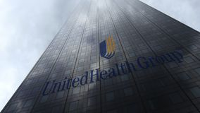 Logo de groupe d'UnitedHealth sur les nuages se reflétants d'une façade de gratte-ciel Rendu 3D éditorial Photographie stock