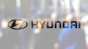 Logo de Hyundai Motor Company sur un verre contre la foule brouillée sur le steet Rendu 3D éditorial Image stock