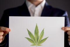 Logo della marijuana della tenuta dell'uomo Fotografie Stock Libere da Diritti