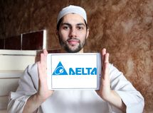 Delta Electronics company logo. Logo of Delta Electronics company on samsung tablet holded by arab muslim man. it is one of the world`s leading producer of power stock images