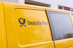Logo from Deutsche Post and DHL on yellow postcar. BERLIN / GERMANY - NOVEMBER 9,2018: Logo from Deutsche Post and DHL on yellow postcar royalty free stock photos