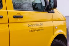 Logo from Deutsche Post and DHL on yellow postcar. BERLIN / GERMANY - NOVEMBER 9,2018: Logo from Deutsche Post and DHL on yellow postcar stock image