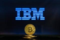 Logo di IBM su uno schermo di computer con una pila di monete di cryptocurency di Bitcoin fotografia stock