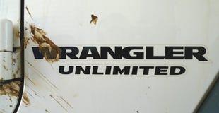 Logo di Jeep Wrangler Unlimited con la spruzzata della sporcizia immagine stock