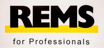Logo di rem Lettere nere dell'autoadesivo sulla parete bianca immagini stock libere da diritti