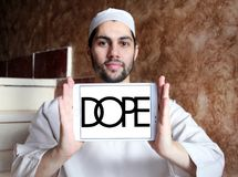 Dope brand logo. Logo of Dope brand on samsung tablet holded by arab muslim man. Dope is a street wear brand. The clothing line is available in boutiques stock images
