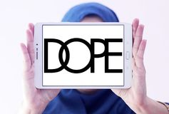 Dope brand logo. Logo of Dope brand on samsung tablet holded by arab muslim woman. Dope is a street wear brand. The clothing line is available in boutiques royalty free stock photo
