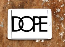 Dope brand logo. Logo of Dope brand on samsung tablet on wooden background. Dope is a street wear brand. The clothing line is available in boutiques worldwide royalty free stock photos
