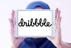Dribbble online community logo. Logo of Dribbble on samsung tablet holded by arab muslim woman. Dribbble is an online community for showcasing user made artwork Royalty Free Stock Image