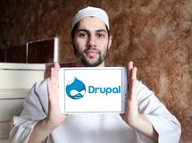 Drupal web framework logo. Logo of Drupal on samsung tablet holded by arab muslim man. Drupal is a free and open source content-management framework written in Royalty Free Stock Images