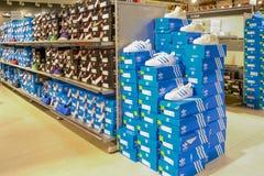 Logo et chaussures d'Adidas dans la fenêtre de boutique Photographie stock libre de droits