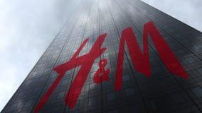Logo för H M på reflekterande moln för en skyskrapafasad Redaktörs- tolkning 3D Royaltyfria Bilder