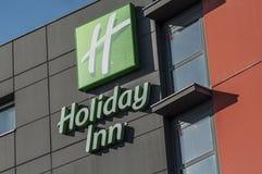Logo för hotell för feriegästgivargård på modern byggnad Holliday Inn är ett americainkedjeföretag av hostelryen royaltyfri bild