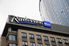 Logo för Radisson blå hotellkedja överst av den nya hotellfasaden arkivbilder
