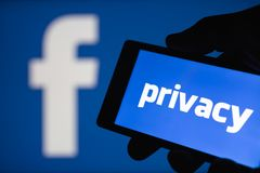Logo of the Facebook blurred on background. The concept of privacy on popular social network. Shallow DOF stock photography