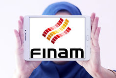 Finam Holdings logo. Logo of Finam Holdings on samsung tablet holded by arab muslim woman. Finam Holdings is a financial services company headquartered in Moscow Stock Photography
